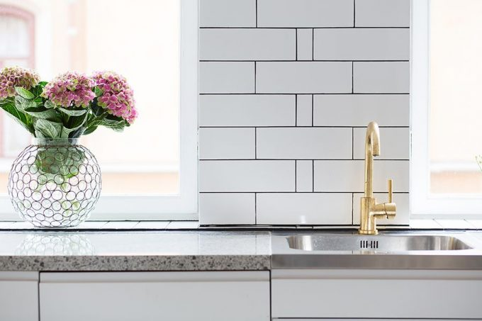 Brass Sink Faucet With A Lovely Flower Vase Next To It And Golden Faucet Design