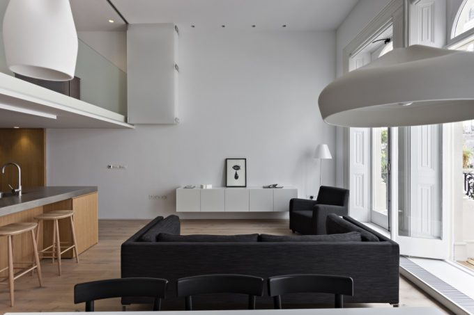 Details White Interior With Black Sofa And Clean Kitchen Design