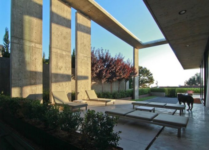 Shaded Outdoor Seating Area With Exposed Wall Pillars And Green Plants