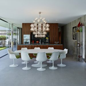 White Rounded Dining Table With Beautiful Chandelier And Wooden Floor Design