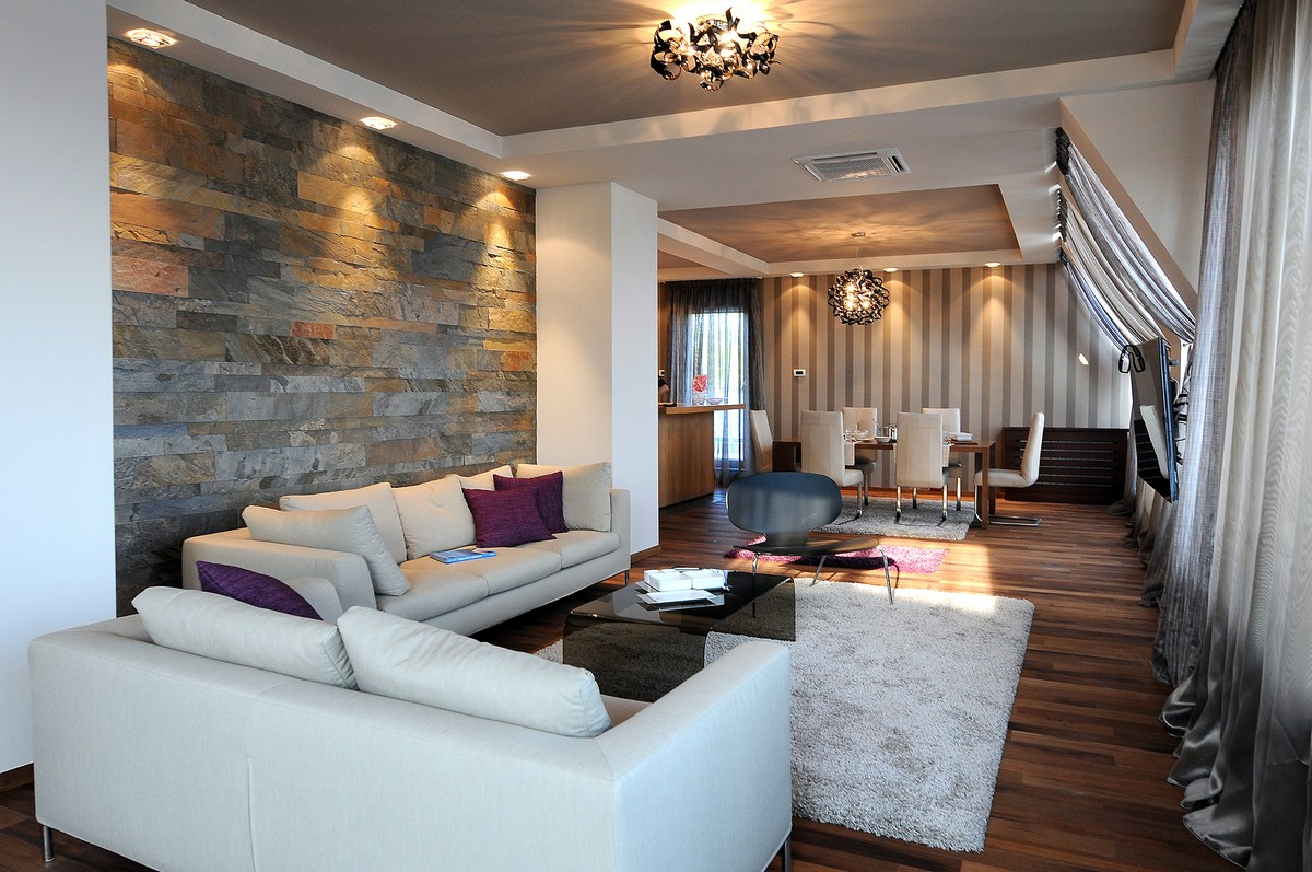 Luxurious Penthouse in Modern and Comfort Design: Apartment In Belgrade Comfortable Living Room With White Sofa Natural Stone Wall And Colorful Curtain