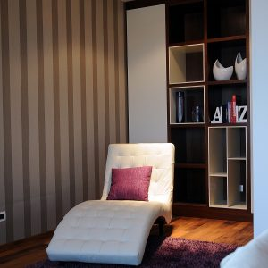 Cozy White Lounge Chair With Purple Rugs And Lined Wallpaper