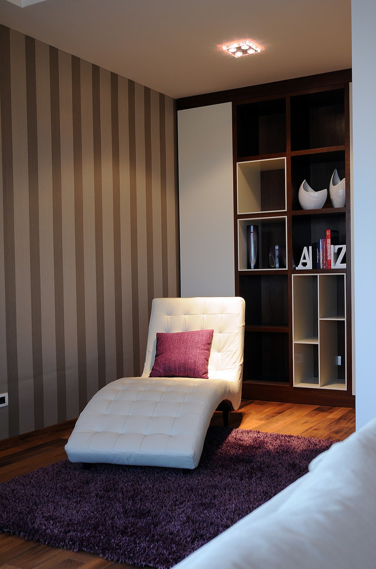 Luxurious Penthouse in Modern and Comfort Design: Cozy White Lounge Chair With Purple Rugs And Lined Wallpaper