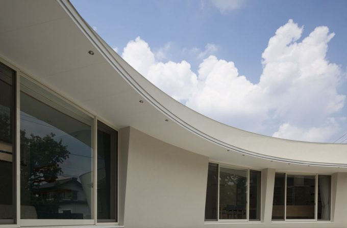 Curving Exterior With White Color And Glass Window Design
