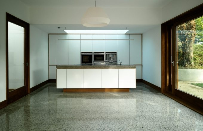 Neat Kitchen With White Countertop And Floor To Ceiling Window