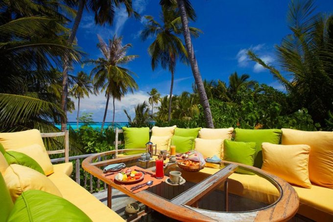 Outdoor Patio With Colorful Sofa And Green Vegetation