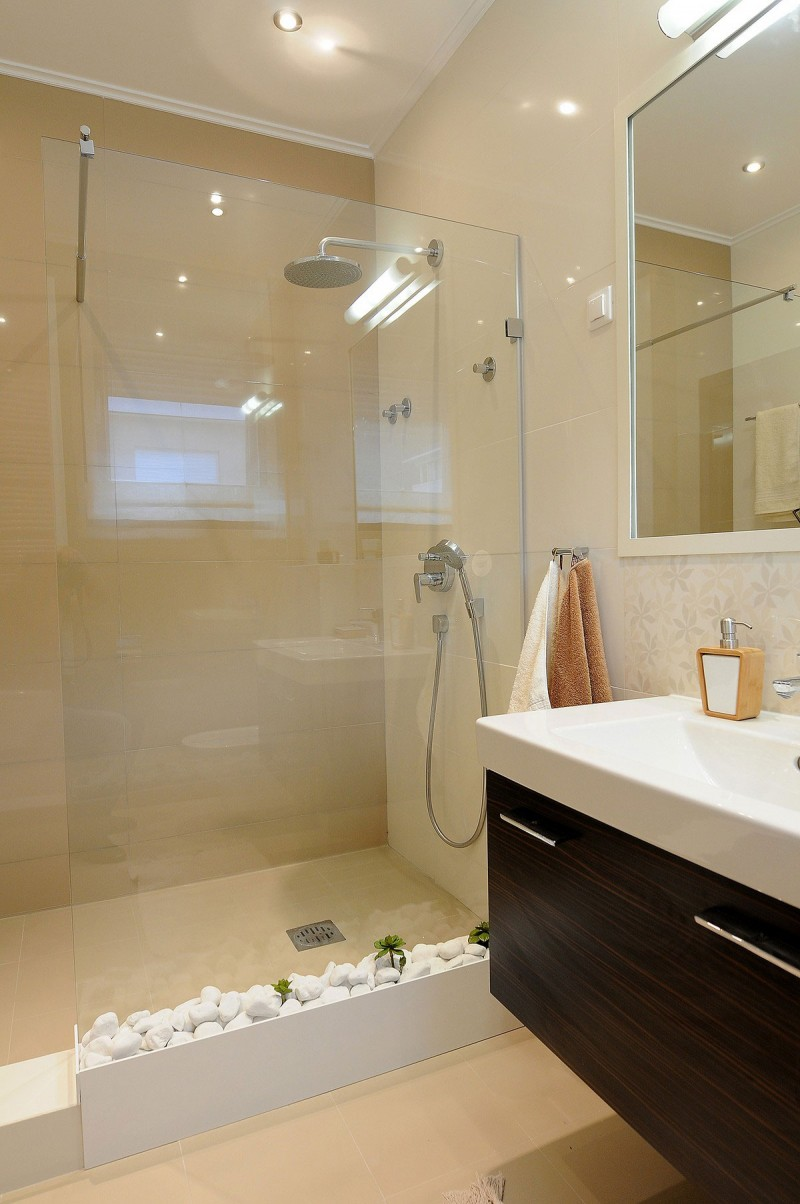 The Shower Space With Glass Partition Next To The Bathroom Vanity