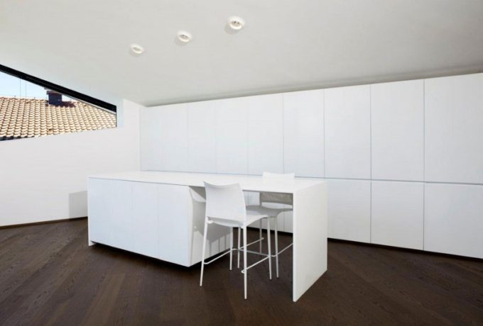 The White Kitchen Island In White Interior And Wooden Floor