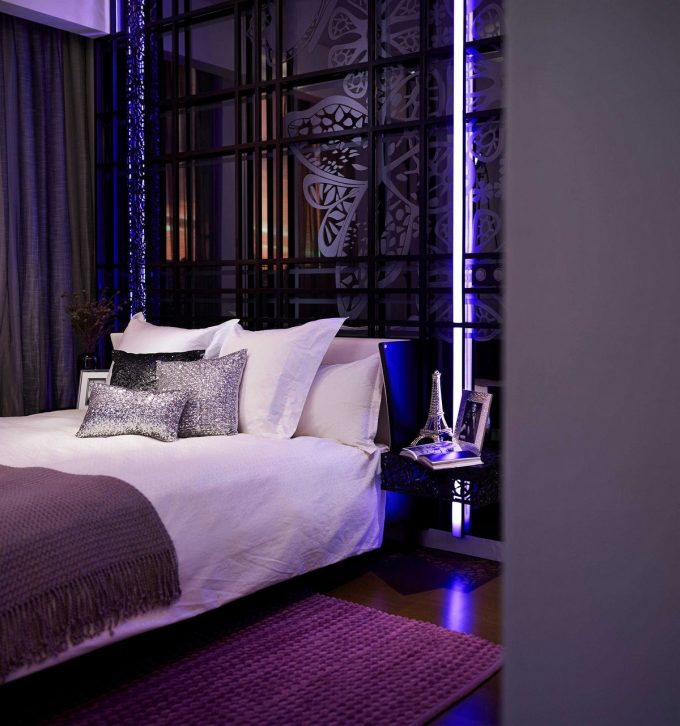White Bed With Artistic Headboard And Purple Lighting
