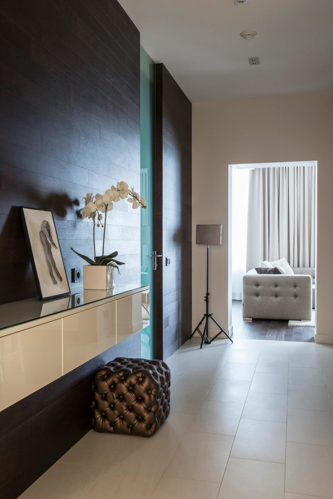 White Tile Flooring With Dark Wooden Wall And Pouf For Room Decor