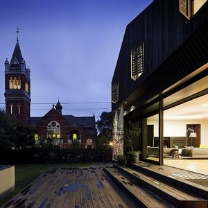 Wooden Backyard Deck And Green Landscaping In Night Facade