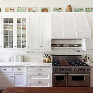 Artwork Atop Cabinets And Glass Door Cabinet In A Traditional Bright Kitchen