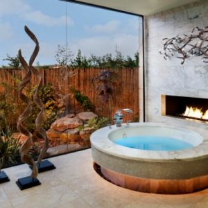 Cool Round Bath Tub Design With An Adjacent Fireplace And Stunning Garden View