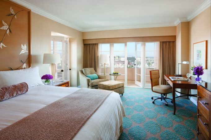 Premier Guestroom Elegant Bed With Blue Patterned Carpet Comfy Lounge Chair And Smal Work Space Decor
