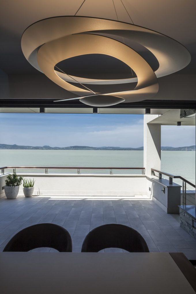 Artistic Terrace Design With Unique Pendant Lamp And Water View