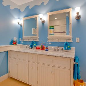 Beautiful Underwater World Theme On The Walls With Unique White Cabinets And Blue Wall Turns This Bathroom Into A World Of Fun