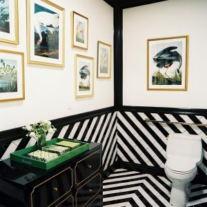 Black Lacquered Chest In A Hollywood Regency Bathroom With Chevron Tiled Bathroom Design