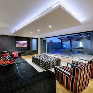 Comfortable Living Room Design With Luxury Black Couch Shiny Yellow Wooden Floor And Folding Door Decor