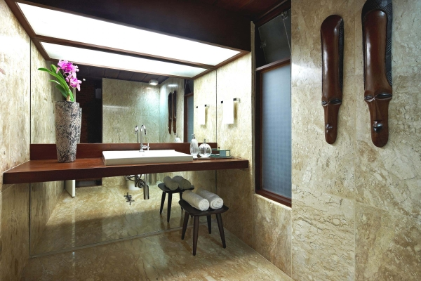 Hawaiian Wood Masks In A Tropical Bathroom Designing With Marble Flooring