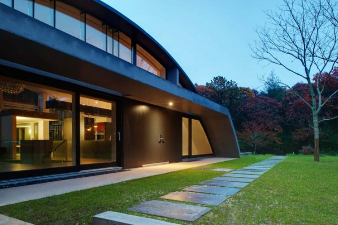 Modern Arc Shape House Design With Modern Exterior Of Transparent Glass And Metal Material