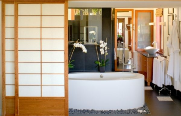 Natural Japanese Bathroom With Oval Bathtub Surrounded By Stone Pebbles And Natural Accessories