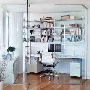 Compact Home Office Space With Glass Wall And Wall Shelves