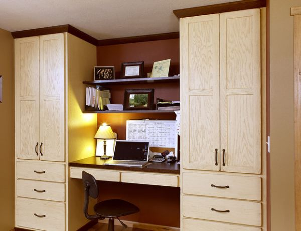 Compact Office Space Nestled Between Large Red Oak Cabinets