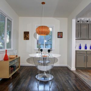 Modern Dining Room With Dark Hard Wood Flooring And Light Wood Console Also White Roung Dining And  Pendant Lamp