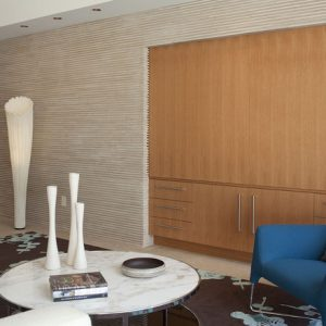 Modern Living Room With White Round Table Blue Armchair Also Different Textures For Walls Plus Wood Closet