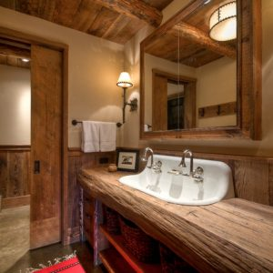 Rustic Bathroom Using Reclaimed Wood Beams And Wooden Pocket Doors Also Sconce Lighting