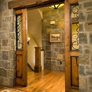 Rustic Entry Using Double Wooden Pocket Doors And Stone Wall Also Wood Flooring