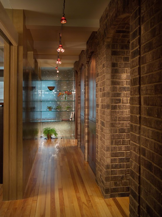 Rustic Hall Way With Wood Flooring And Picture Rail Lighting Also Brick Wall