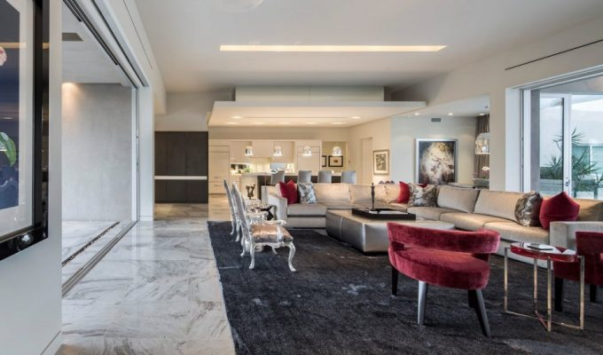 Airy And Spacy Family Room With Beige Sofa And Ottoman Table Also Red Arm Chair With Dark Grey Rugs Below