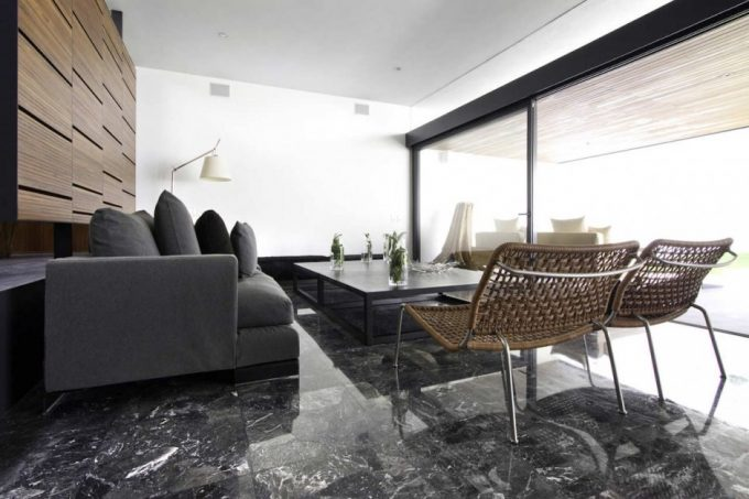 Beautiful Dark Granite Floor In Open Living Room That Use Rattan Chairs And Modern Grey Couch Also Sliding Glass Doors