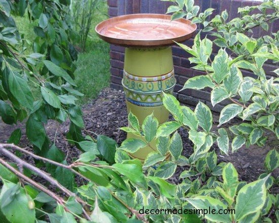 Beautiful Garden With Steel Designer Bird Baths And Small Plants And Green Yellow Stands