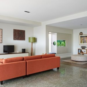 Cool Details Design Living Room With Orange Sofa Facing The TV's Rack And White Wall Also White Ceiling Plus Grey Floor