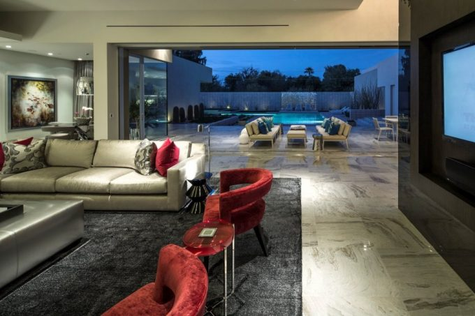 Lovely Open Living Room Design With Modern Dark Sofa With Rugs Area Also Wide Glass Door With Beautiful Courtyard View