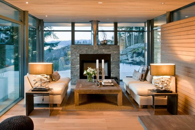 Modern Cabin With Floor To Ceiling Windows And Stone Fireplace Also White Sofa And Small Side Table With Table Lights And Wood Floor Also Ceiling