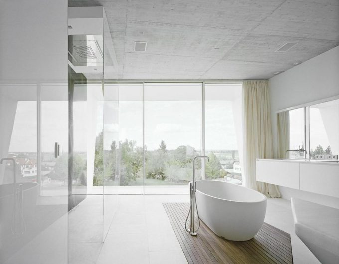 Stunning White Bathroom Design With White Tub And Glossy White Cabinet Also Glass Window And Concrete Ceiling