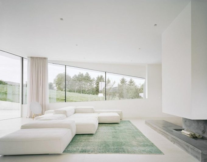 Sunroom Living Room With Luxury White Sofa And Green Rugs Also Wide Glass Windows