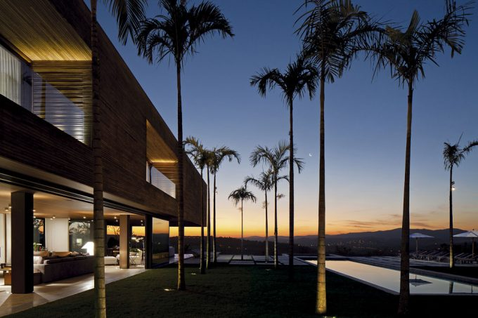 View Evening Of Modern Two Storey House In Brazil With Wood Exterior And Bright Interior Lighting Also Palm Trees In Open Landscape Design