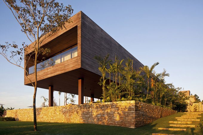 Volume Side Facade With Earthy Exterior Design Using Natural Stone Brick And Wood Exterior With Sloping Landscape Design