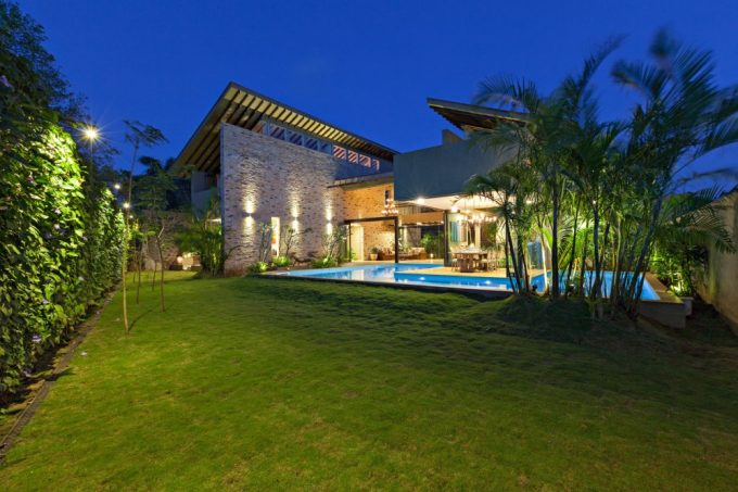 Beautiful Garden View With Growing Plants At The Fence And Green Lawn Also Infinity Pool And Completed With Garden Lighting