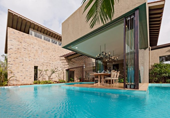 Beautiful Open Dining Place With Luxury Dining Furniture And Chandeliers Also Folding Glass Doors Plus Peaceful Blue Pool View