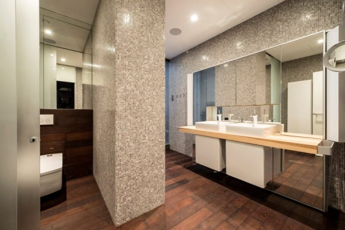 Beautiful Pixeled Wall Bathroom Design With Wooden Palette Floor And White Vanity Plus Wide Mirrors