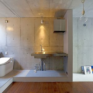 Contemporary Bathroom With Industrial Elements By Atelier Tekuto Using Concrete Wall Panel And Stainless Steel Sink Also White Closet Plus Down Lighting And Big Bulb Lamp