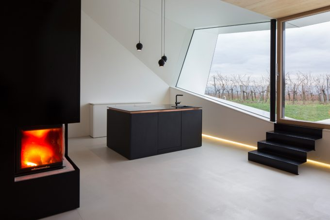 Dark Fireplace And Black Kitchen Also Pendant Lamps Plus Sharp Cut Windows With Vineyard View