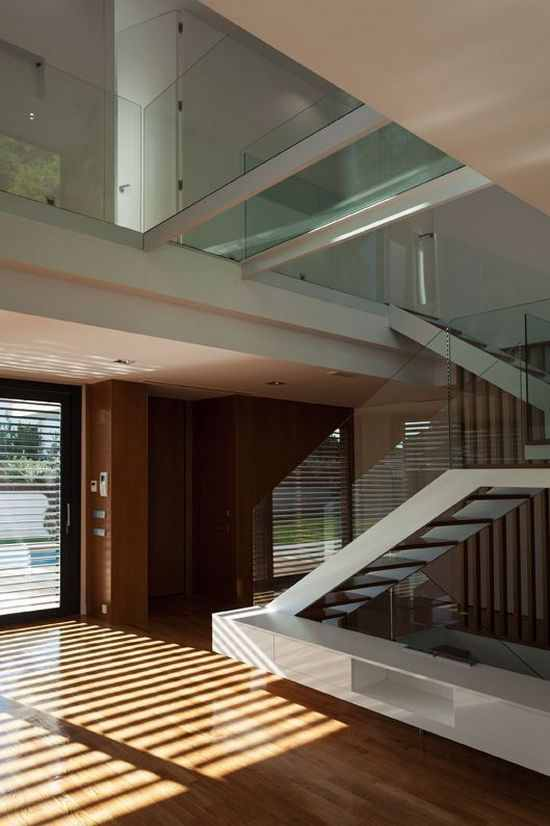 Glass Handrail And Modern Staircase Also Wood Flooring With Glass Windows Surroung The Living Room