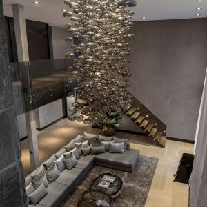 Magnificent Interior With Stunning Chandelier And Grey Sofa Also Dark Rugs In Spacy Family Room