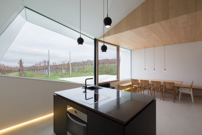 Minimalist Kitchen Design Idea With Wood Furniture And Black Kitchen Island Also Floor Neon Lighting Plus Geometric Window Cut